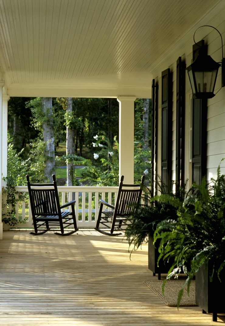 Veranda of elegant country house with dark wooden rocking chairs