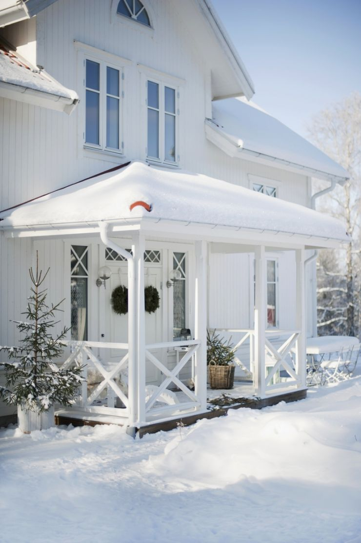 White wooden house with roofed porch in winter atmosphere