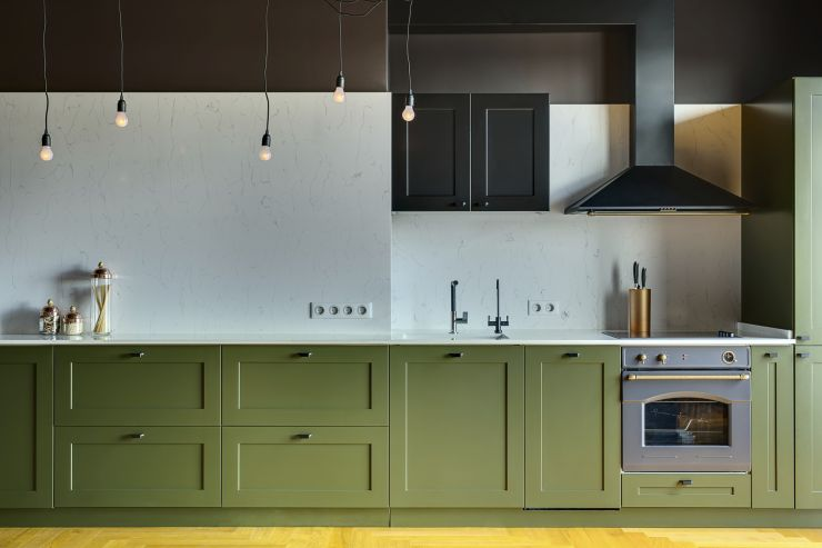 Kitchen in a modern style with a light tabletop with sink, cooker, oven, kitchen accessories. Under tabletop there are green drawers. Over tabletop there is kitchen hood, cupboard and glowing lamps.